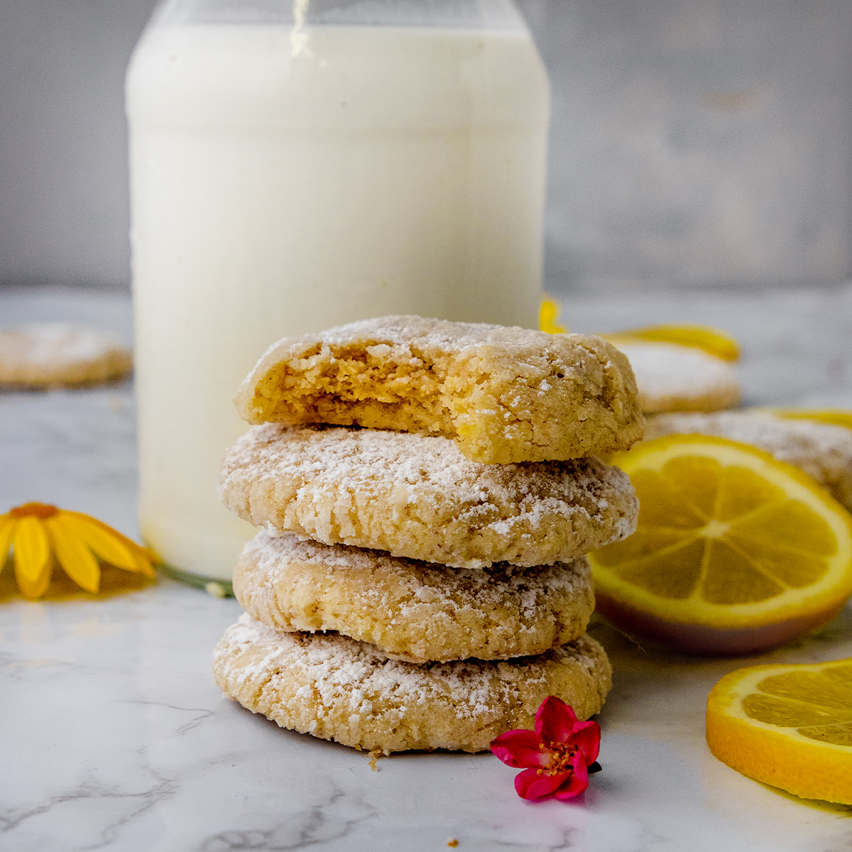 stack of bright vegan lemon crinkle cookies with a bite taken out next to a glass of milk