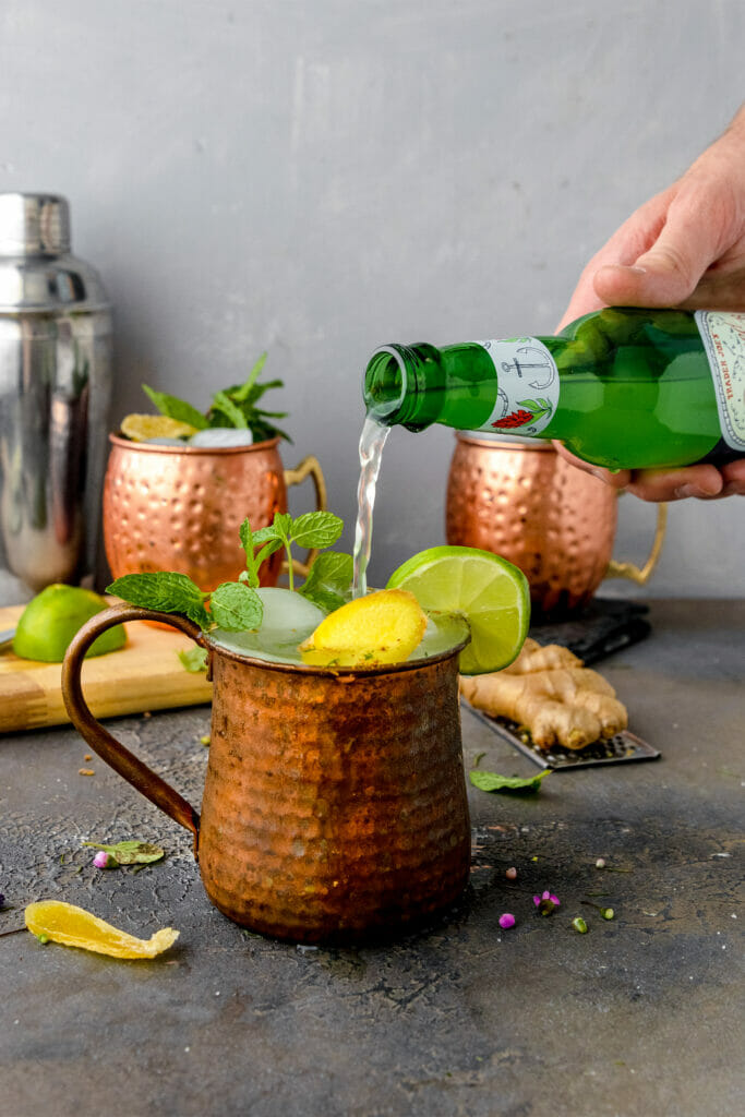 hand pouring ginger beer into copper moscow mule mug