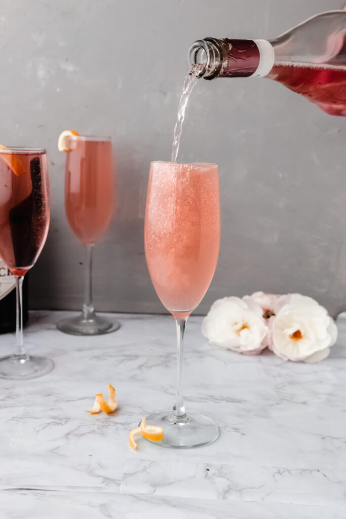 sparkling rose pouring into a champagne flute of rose french 75