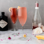 two rose french 75 cocktails on a marble table next to a bottle of wine and a bottle of gin
