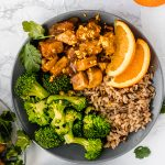 orange slices with orange tofu broccoli and rice on a grey plate