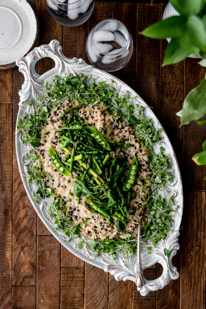 overhead shot of asparagus barley risotto and a wooden table with two glasses of water