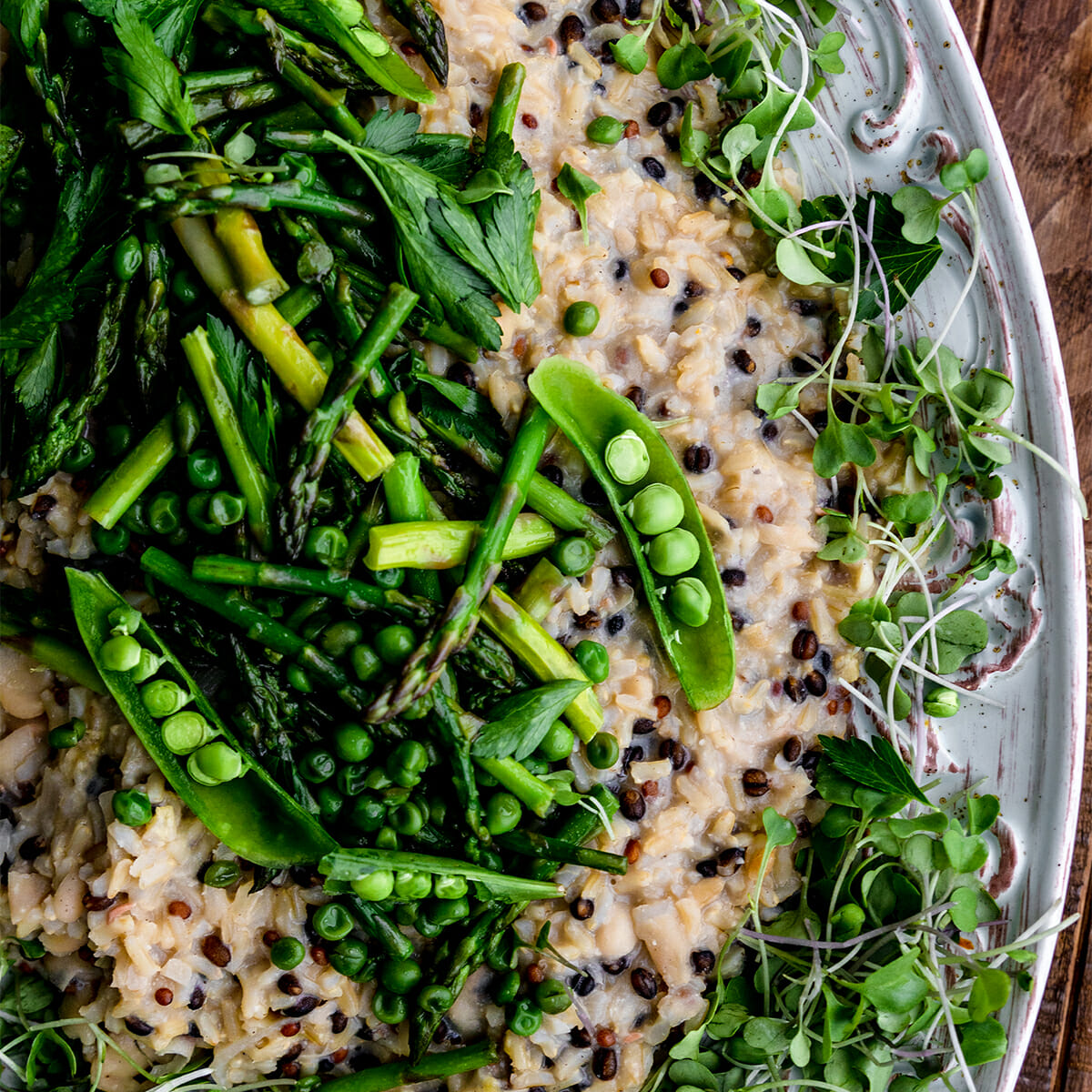 close up of barley risotto topped with asparagus and peas on a white plate