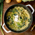 overhead shot of vegan colcannon with leeks in a white pot on a wooden table