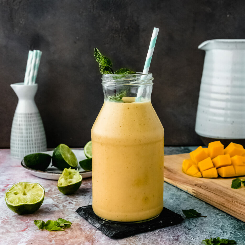 glass jar of vegan mango lassi on a table next to mango pieces