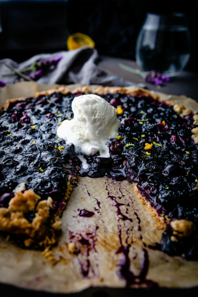 side view of berry galette with a slice taken out and a scoop of vanilla ice cream