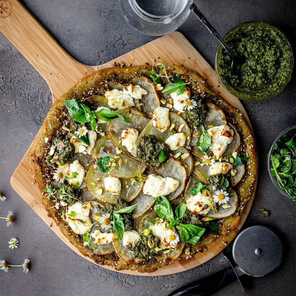 overhead shot of vegan pesto potato pizza on a pizza peel next to a bowl of pesto and some fresh herbs