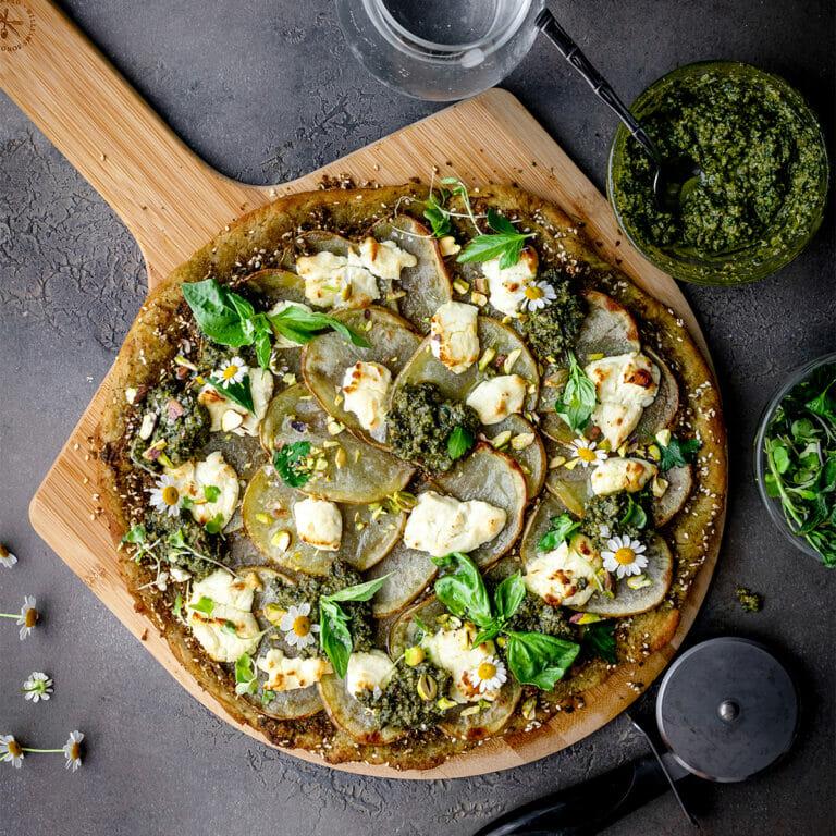 overhead shot of vegan pesto potato pizza on a pizza peel next to a bowl of pesto and some fresh herbs