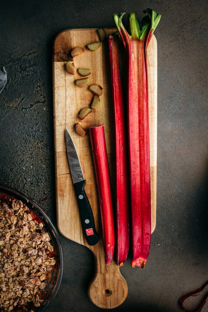 two stalks of red rhubarb with one sliced stalk on a wooden tray with a knife