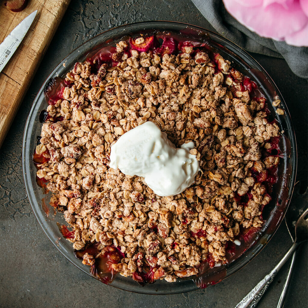 overhead shot of brown butter rhubarb crumble on a stone table with two scoops of vanilla ice cream