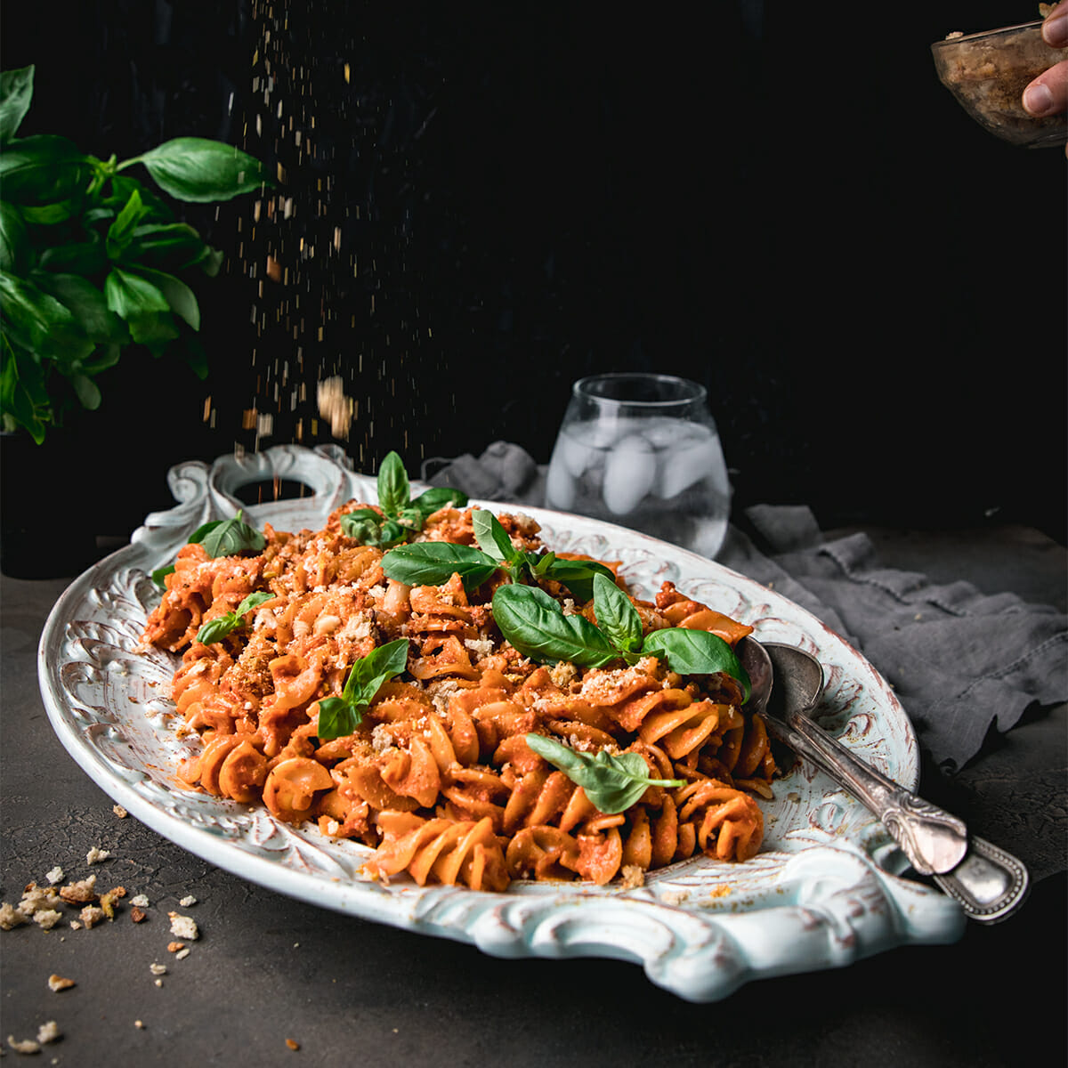 breadcrumbs sprinkled onto a plate of roasted red pepper pasta salad