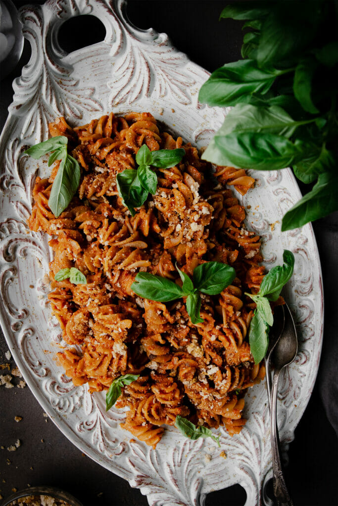 overhead shot of romesco pasta salad on a white place with basil