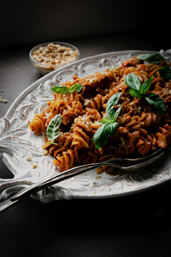 side view of roasted red pepper pasta salad on a white plate with a silver spoon
