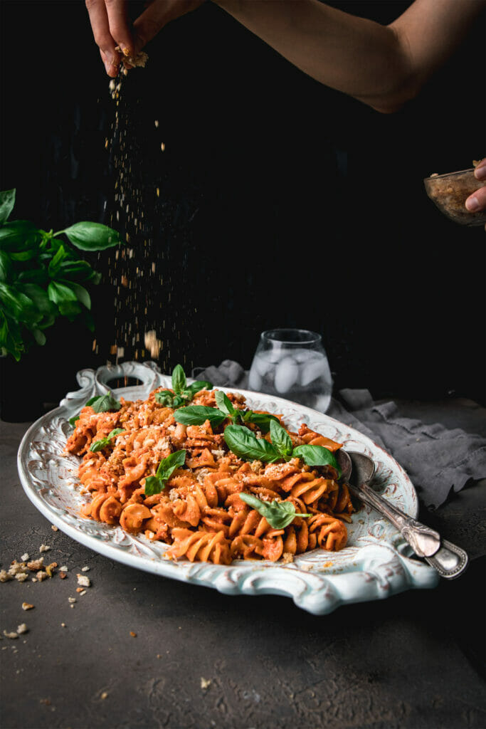 hand holding breadcrumbs sprinkled onto a plate of roasted red pepper pasta salad