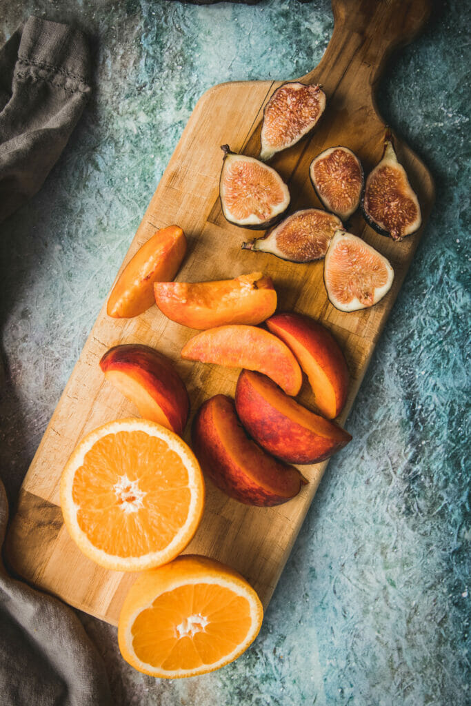cutting board with chopped oranges, peaches, and figs shot from overhead