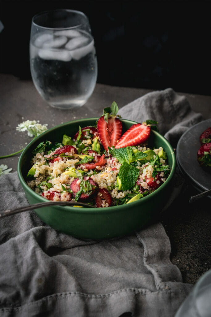 side view of green bowl of strawberry quinoa salad with a silver spoon on a grey table