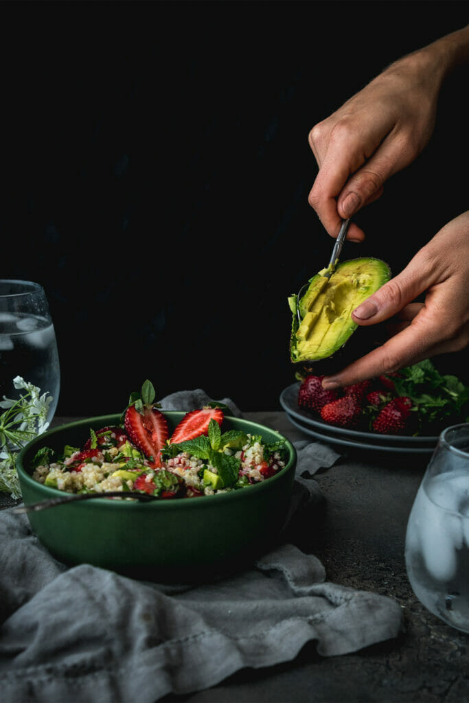 hand scooping avocado into a bowl of strawberry quinoa salad