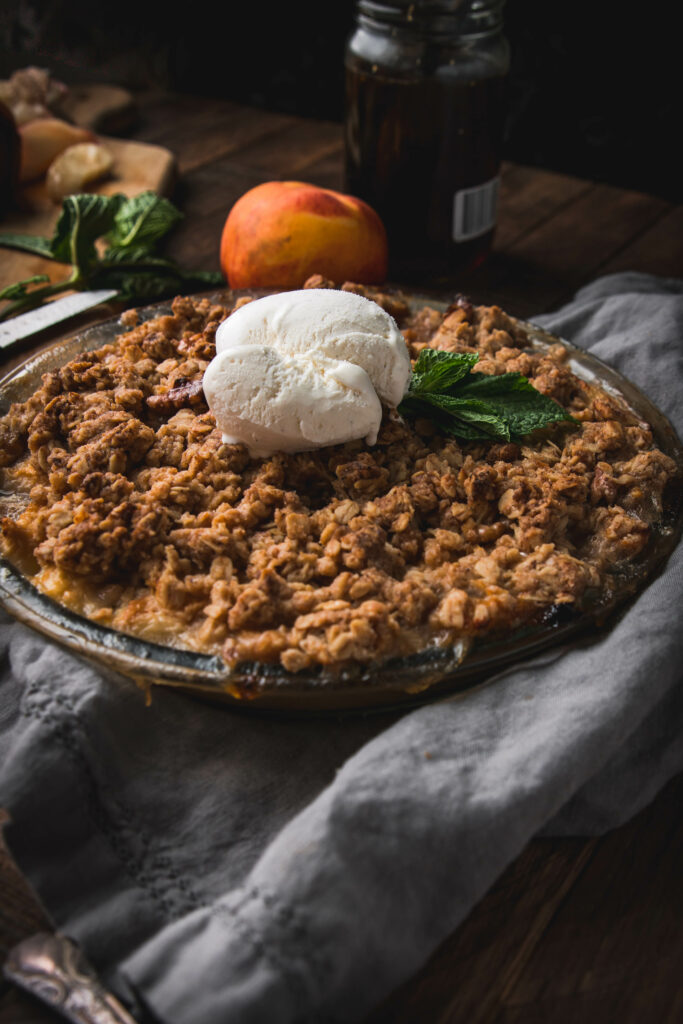 side view of brown butter peach crumble with ice cream on top