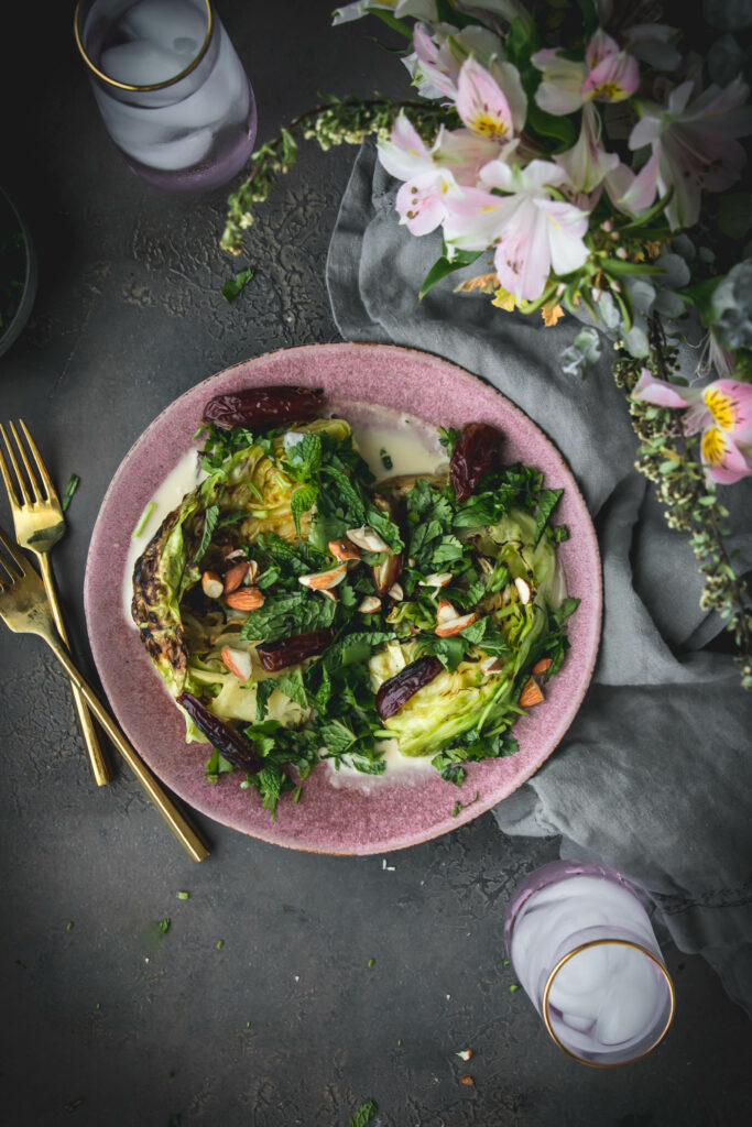 overhead shot of green grilled cabbage on a plate next to a vase of flowers