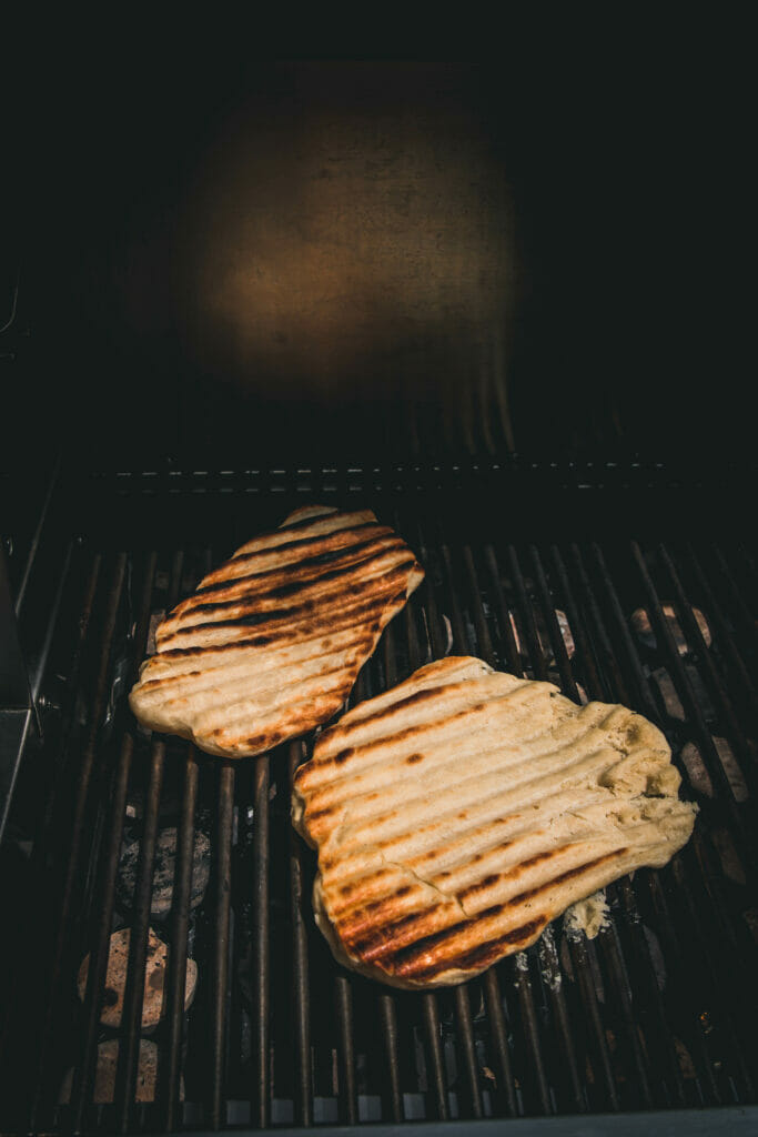 Two flatbreads being grilled
