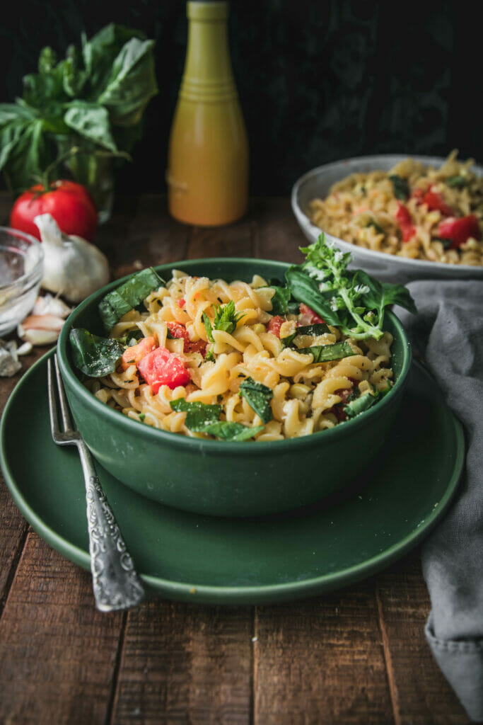 side view of creamy sweet corn pasta  in a green bowl