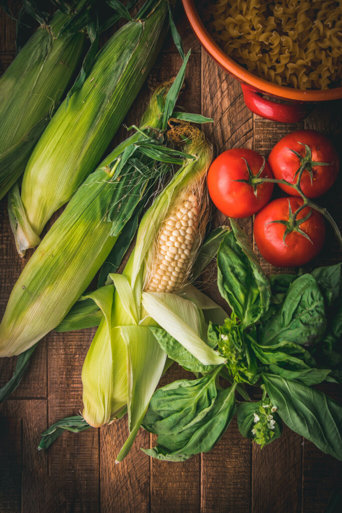 wooden table with three ears of corn and three tomatoes shot from above