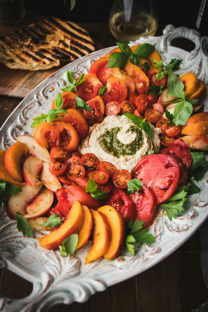 close up of sliced peaches and cherry tomatoes on an appetizer plate