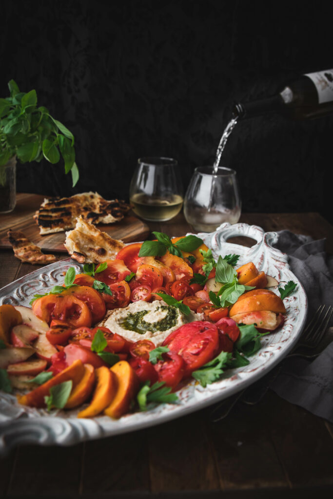 wine poured into a glass behind a tray of fresh tomatoes and sliced peaches in a caprese salad