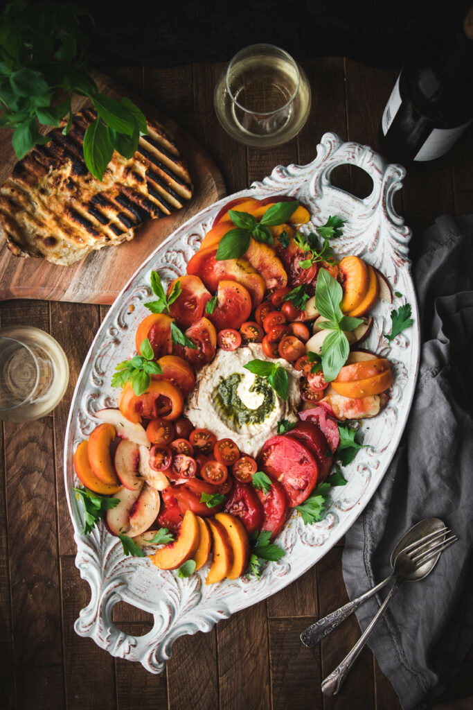 grilled flatbread next to an heirloom tomato and peach summer salad