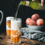 hand pouring a jar of ginger beer into a glass of peach crumble ice cream floats