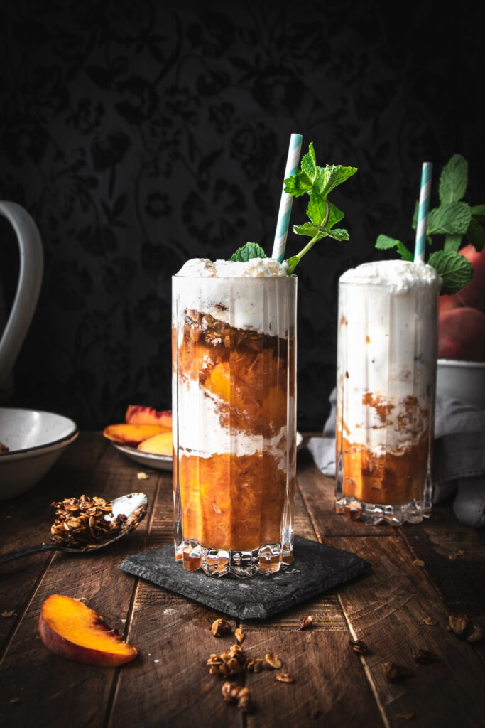 two glasses of peach crumble ice cream floats topped with mint on a wooden table