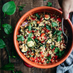 hand with a spoon reaching into a bowl of roasted ratatouille couscous on a wooden table