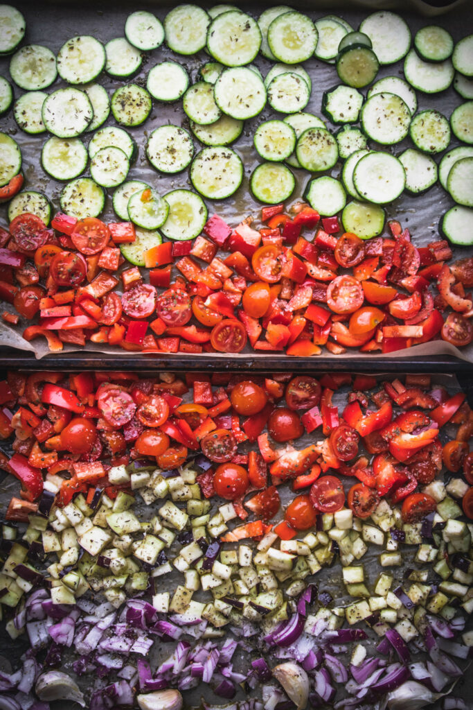 overhead shot of two baking sheets with roasted ratatouille ingredients of zucchini, cherry tomatoes, red peppers, and eggplant