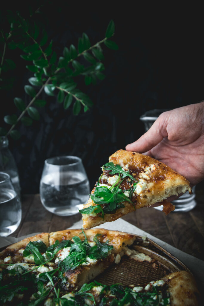hand holding a slice of fig jam bianca pizza on a wooden table