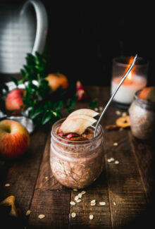 side view of apple pie overnight oats on a wooden table next to an apple