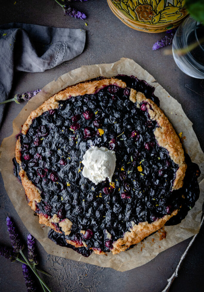 overhead shot of vegan berry galette with a scoop of ice cream in the center on a piece of parchment