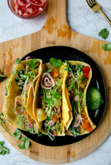overhead shot of three kale potato tacos on a black plate on a wooden board