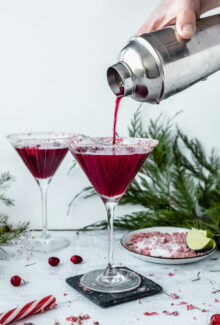 red clausmopolitan pouring into martini glass out of a silver shaker