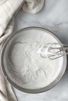 overhead shot of coconut whipped cream in a silver bowl next to a hand mixer