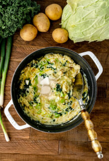overhead shot of vegan colcannon with leeks in a white pot on a wooden table with a spoon
