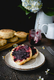 sliced open english muffin spread with blackberry jam
