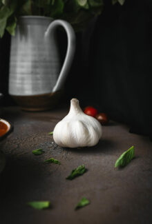 a whole head of garlic on a stone board next to some basil leave