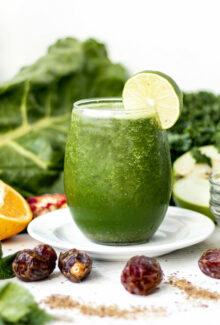 green smoothie surrounded by fresh fruit