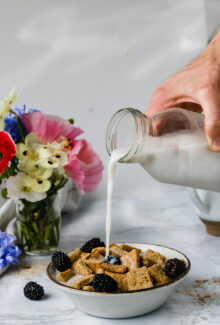 hand holding milk jug pouring into a bowl of homemade cereal with flowers in the background