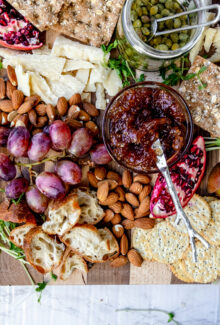 overhead shot of fig jam on a vegan cheese board with a sliver knife