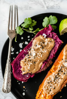 black plate with two instant pot purple sweet potatoes next to a fork