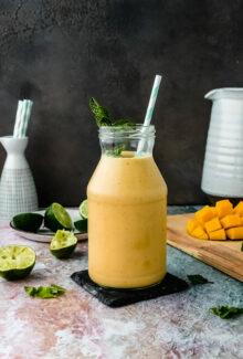 glass jar of vegan mango lassi on a table next to mango pieces