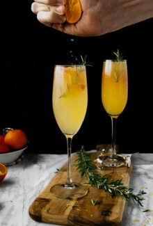 hand squeezing orange juice into a mimosa flute glass