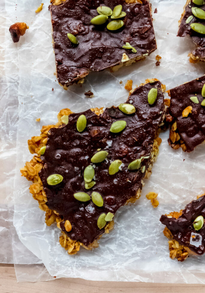 close up overhead shot of oat granola bar with a dark chocolate coating and pumpkin seeds on top