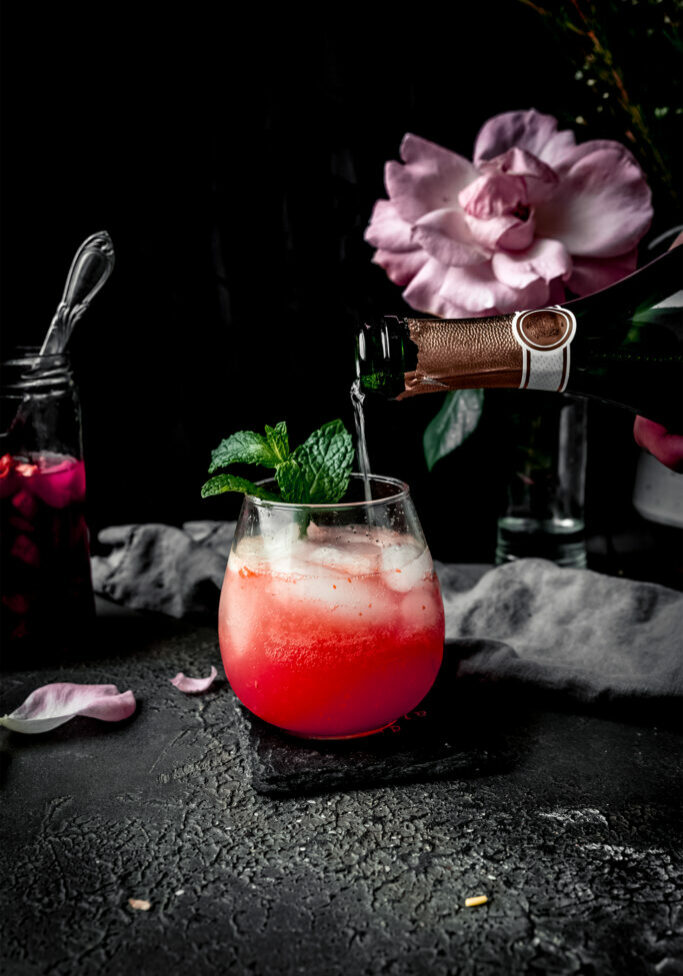 champagne pouring into a glass of sparkling rhubarb shrub